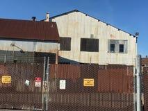 Ζαρωμένα βιομηχανικά κτήρια ακίνδυνα πίσω από την περίφραξη που ολοκληρώνεται με οδοντωτό - καλώδιο Στοκ φωτογραφίες με δικαίωμα ελεύθερης χρήσης