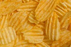 Ζαρωμένα τσιπ πατατών στο υπόβαθρο Στοκ Εικόνες