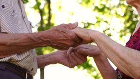 Ζαρωμένα χέρια ενός ηλικιωμένου ζεύγους, κινηματογράφηση σε πρώτο πλάνο απόθεμα βίντεο