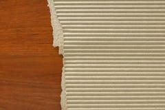 Ζαρωμένο χαρτόνι στο ξύλινο επιτραπέζιο υπόβαθρο Στοκ εικόνα με δικαίωμα ελεύθερης χρήσης