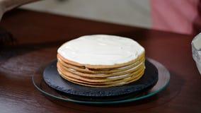 Ζαχαροπλάστης γυναικών που κατασκευάζει το κέικ με την κρέμα βανίλιας φιλμ μικρού μήκους