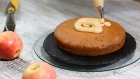 Ζαχαροπλάστης με την τσάντα ζύμης που συμπιέζει την κρέμα στο κέικ στην κουζίνα r απόθεμα βίντεο