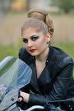 Ζαλίζοντας, το μοντέρνο, επικίνδυνο, σοβαρό κορίτσι ποδηλατών με τα μάτια smokey makeup, σύνθεση, κόκκινα χείλια με το σακάκι δέρ Στοκ Εικόνες