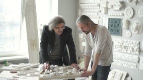 Ζευγάρι των αρσενικών σχεδιαστών που συζητούν τα φορμάροντας δείγματα απόθεμα βίντεο