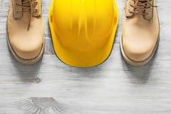 Ζευγάρι των αδιάβροχων μποτών που στηρίζονται το κράνος στο ξύλινο constru πινάκων Στοκ φωτογραφία με δικαίωμα ελεύθερης χρήσης
