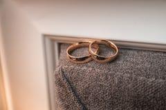 Ζευγάρι των γαμήλιων χρυσών δαχτυλιδιών σε ένα καφετί υπόβαθρο τοίχων Στοκ Εικόνες