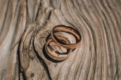 Ζευγάρι των γαμήλιων χρυσών δαχτυλιδιών στο κίτρινο ξύλινο αγροτικό υπόβαθρο Στοκ Φωτογραφία
