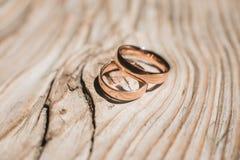 Ζευγάρι των γαμήλιων χρυσών δαχτυλιδιών στο κίτρινο ξύλινο αγροτικό υπόβαθρο Στοκ φωτογραφία με δικαίωμα ελεύθερης χρήσης