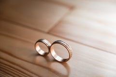 Ζευγάρι των γαμήλιων χρυσών δαχτυλιδιών στο κίτρινο ξύλινο πάτωμα Στοκ Εικόνες
