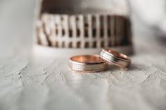 Ζευγάρι των γαμήλιων χρυσών δαχτυλιδιών στο ραγισμένο δέρμα Στοκ Εικόνες
