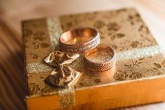 Ζευγάρι των γαμήλιων χρυσών δαχτυλιδιών στο χρυσό κιβώτιο δώρων Στοκ Εικόνες