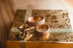 Ζευγάρι των γαμήλιων χρυσών δαχτυλιδιών στο χρυσό κιβώτιο δώρων Στοκ Φωτογραφίες