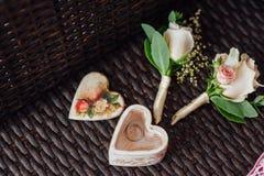 Ζευγάρι των γαμήλιων δαχτυλιδιών με τη μπουτονιέρα του νεόνυμφου Στοκ φωτογραφία με δικαίωμα ελεύθερης χρήσης