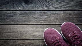 Ζευγάρι των κόκκινων πάνινων παπουτσιών στο ξύλινο υπόβαθρο Αθλητισμός και BA ικανότητας Στοκ Φωτογραφίες
