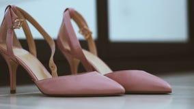 Ζευγάρι των κλασσικών ρόδινος-μπεζ γαμήλιων παπουτσιών γυναικών στο πάτωμα - defocus αλλαγής για να στραφεί απόθεμα βίντεο