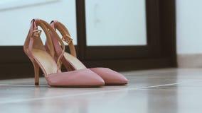 Ζευγάρι των κλασσικών ρόδινος-μπεζ γαμήλιων παπουτσιών γυναικών στο πάτωμα - defocus αλλαγής για να στραφεί φιλμ μικρού μήκους
