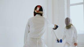 Ζευγάρι των ξιφομάχων που πραγματοποιούν τις αμυντικές ασκήσεις πρακτικής να περιφράξει μέσα το στούντιο στο εσωτερικό απόθεμα βίντεο