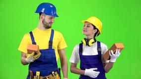 Ζευγάρι των οικοδόμων που κρατούν ένα τούβλο στα χέρια τους και που παρουσιάζουν δάχτυλά τους πράσινη οθόνη κίνηση αργή απόθεμα βίντεο
