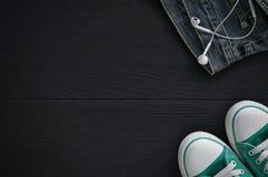 Ζευγάρι των πάνινων παπουτσιών, ένα τεμάχιο των τζιν και των ακουστικών στο Μαύρο Στοκ Φωτογραφία
