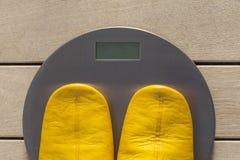 Ζευγάρι των παντοφλών στην κλίμακα βάρους Στοκ Φωτογραφία