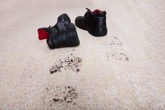 Ζευγάρι των παπουτσιών με τη λάσπη στο πάτωμα ταπήτων Στοκ Εικόνα
