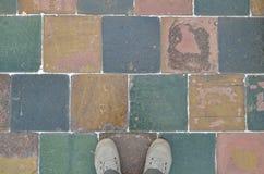 Ζευγάρι των ποδιών στα παπούτσια καμβά checkerboard στο πεζοδρόμιο στοκ εικόνες με δικαίωμα ελεύθερης χρήσης