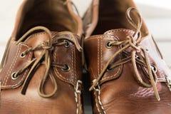 Ζευγάρι των φθαρμένων καφετιών περιστασιακών παπουτσιών δέρματος μπροστά από το άσπρο ξύλινο υπόβαθρο Στοκ Φωτογραφίες