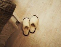 Ζευγάρι των χνουδωτών άνετων παντοφλών στο πάτωμα στην κρεβατοκάμαρα στοκ φωτογραφίες