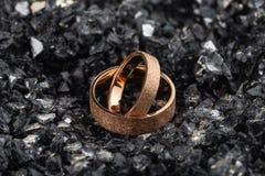 Ζευγάρι των χρυσών γαμήλιων δαχτυλιδιών με την κατασκευασμένη επιφάνεια στα shards του γυαλιού στοκ εικόνες