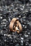 Ζευγάρι των χρυσών γαμήλιων δαχτυλιδιών με την κατασκευασμένη επιφάνεια στα shards του γυαλιού στοκ εικόνες με δικαίωμα ελεύθερης χρήσης