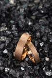 Ζευγάρι των χρυσών γαμήλιων δαχτυλιδιών με την κατασκευασμένη επιφάνεια στα shards του γυαλιού στοκ φωτογραφίες με δικαίωμα ελεύθερης χρήσης