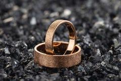 Ζευγάρι των χρυσών γαμήλιων δαχτυλιδιών με την κατασκευασμένη επιφάνεια στα shards του γυαλιού στοκ εικόνα