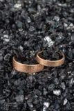 Ζευγάρι των χρυσών γαμήλιων δαχτυλιδιών με την κατασκευασμένη επιφάνεια στα shards του γυαλιού στοκ φωτογραφία με δικαίωμα ελεύθερης χρήσης