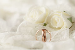Ζευγάρι των χρυσών γαμήλιων δαχτυλιδιών πέρα από την κάρτα πρόσκλησης που διακοσμείται με τη δαντέλλα Στοκ φωτογραφία με δικαίωμα ελεύθερης χρήσης