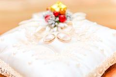 Ζευγάρι των χρυσών γαμήλιων δαχτυλιδιών σε ένα όμορφο μαξιλάρι Στοκ Φωτογραφίες