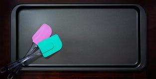 Ζευγάρι χρωματισμένο Spatula σε έναν Polytetrafluoroethylene δίσκο ψησίματος Στοκ Εικόνες