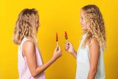 Ζευγαρώνει τα κορίτσια με τη ζωηρόχρωμη καραμέλα που έχει τη διασκέδαση μαζί, απομονωμένη στο κίτρινο υπόβαθρο στοκ φωτογραφία με δικαίωμα ελεύθερης χρήσης
