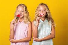 Ζευγαρώνει τα κορίτσια με τη ζωηρόχρωμη καραμέλα που έχει τη διασκέδαση μαζί, απομονωμένη στο κίτρινο υπόβαθρο στοκ εικόνα με δικαίωμα ελεύθερης χρήσης
