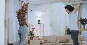 Ζευγών χαμόγελου μεγάλο και συγκινημένο αστείο σε ένα καινούργιο σπίτι αφότου τελείωσαν στη μεταφορά όλης της ουσίας αυτοί που αι απόθεμα βίντεο