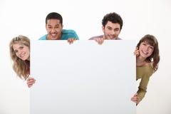 Ζεύγη που στέκονται με τη διαφήμιση του χαρτονιού Στοκ Εικόνες