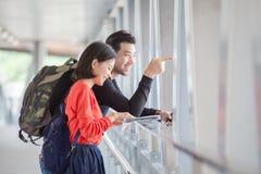 Ζεύγη του νεώτερων διακινούμενων άνδρα και της γυναίκας που κοιτάζουν στον ταξιδιώτη γ Στοκ εικόνα με δικαίωμα ελεύθερης χρήσης