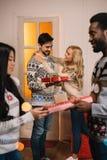 Ζεύγη Multiethnic που ανταλλάσσουν τα δώρα Χριστουγέννων Στοκ Εικόνα