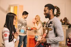 Ζεύγη Multiethnic που ανταλλάσσουν τα δώρα Χριστουγέννων Στοκ Εικόνες