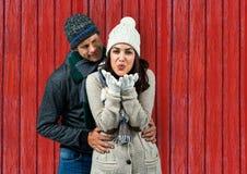 ζεύγος: αυτή που στέλνει ένα φιλί και αυτός που κοιτάζει αυτή με το κόκκινο ξύλινο υπόβαθρο Στοκ φωτογραφία με δικαίωμα ελεύθερης χρήσης