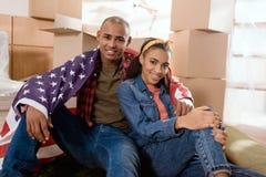 ζεύγος αφροαμερικάνων με τη συνεδρίαση Ηνωμένων σημαιών πάτωμα στο νέο σπίτι στοκ εικόνες