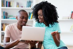 Ζεύγος αφροαμερικάνων που ψάχνει την εργασία on-line με τον υπολογιστή στοκ εικόνα