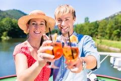 Ζεύγος ερωτευμένο στην κρουαζιέρα ποταμών που πίνει coctails το καλοκαίρι στοκ εικόνα