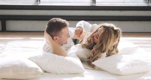 Ζεύγος ερωτευμένο στο κρεβάτι Ο τύπος και το κορίτσι χαμογελούν ο ένας τον άλλον, το κοίταγμα στα μάτια και το αγκάλιασμα απόθεμα βίντεο