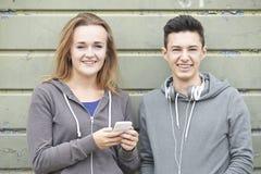 Ζεύγος εφήβων που μοιράζεται το μήνυμα κειμένου στο κινητό τηλέφωνο στοκ φωτογραφία με δικαίωμα ελεύθερης χρήσης
