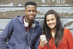Ζεύγος εφήβων που μοιράζεται το μήνυμα κειμένου στο κινητό τηλέφωνο στοκ εικόνες